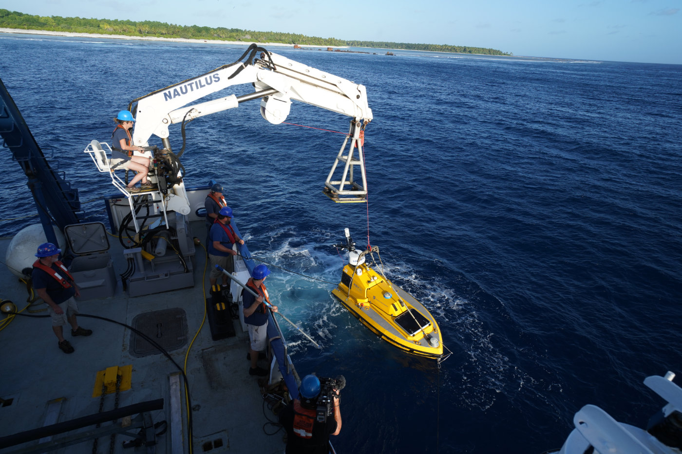 A remotely operated vehicle is lowered from the side of the E/V Nautilus