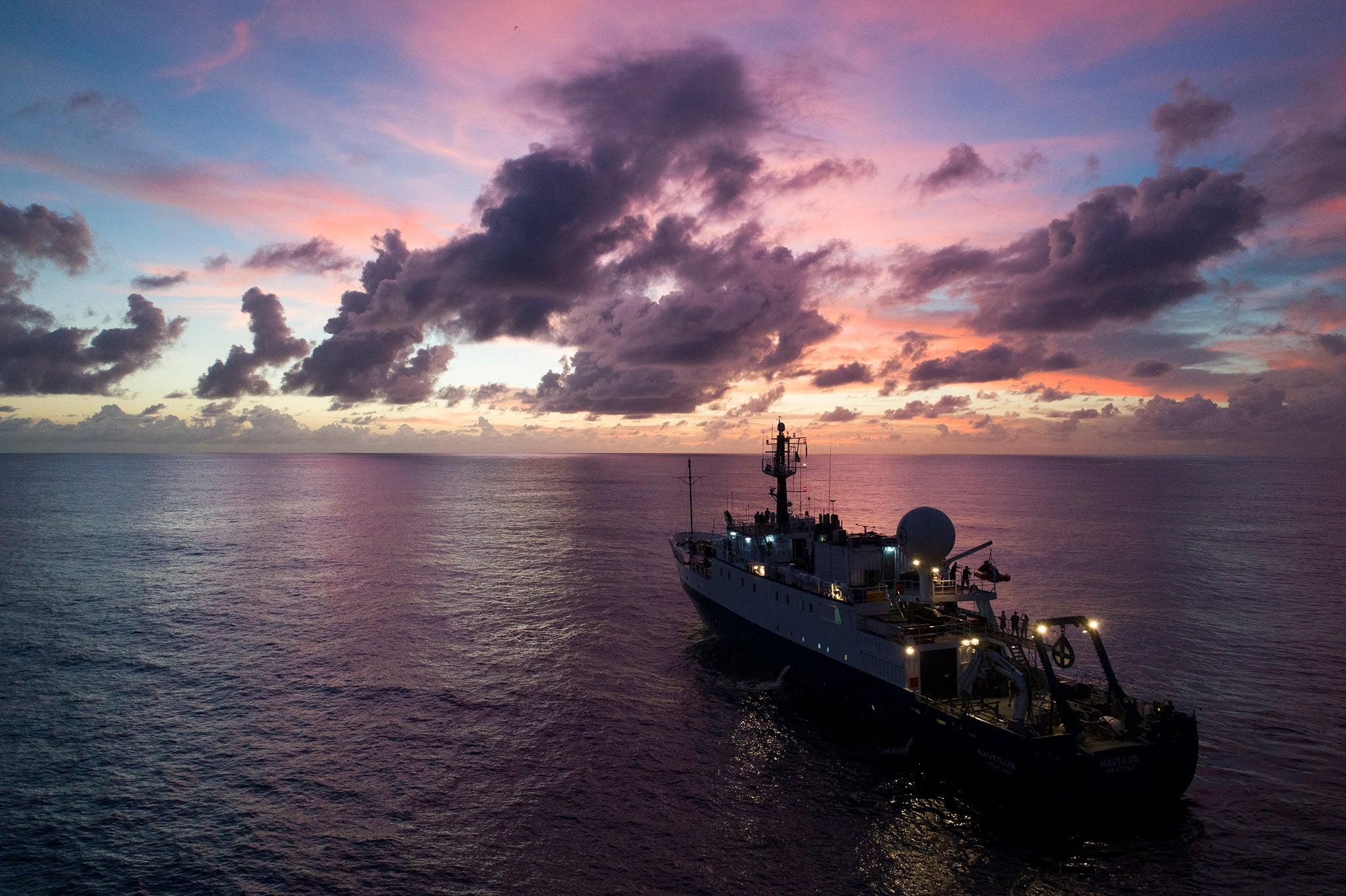 The E/V Nautilus at sea at sunset