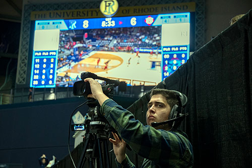 Communications student filming women's basketball game