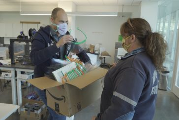 Dominik Brysch hands a box of face shields to a fire rescue worker