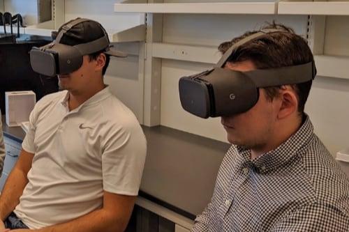 Matthew Constant and Noah Johnson wearing Google Daydream headsets in Bin Li's research laboratory