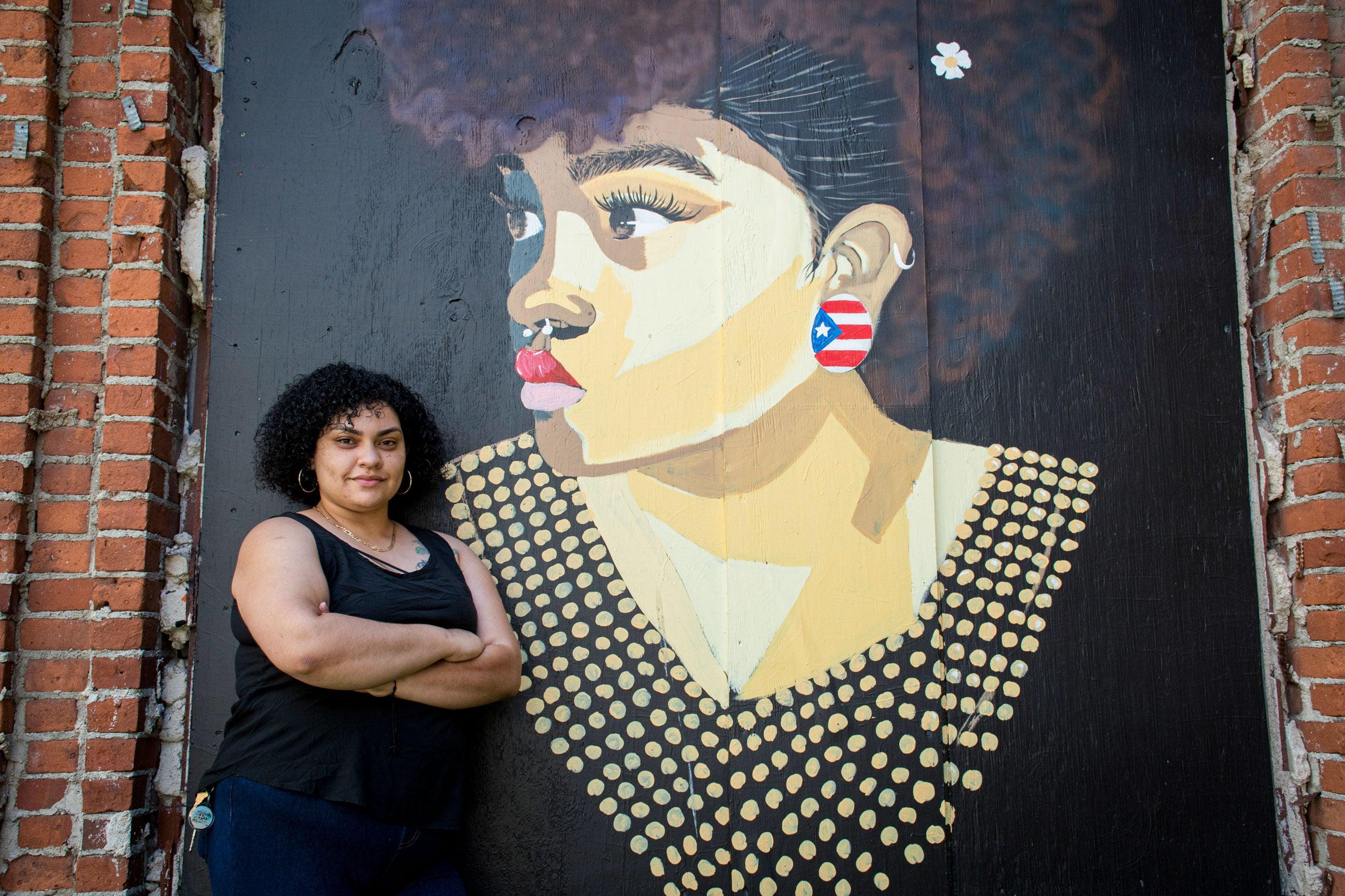 """Angela Gonzalez, """"agonza"""" in front of her mural"""