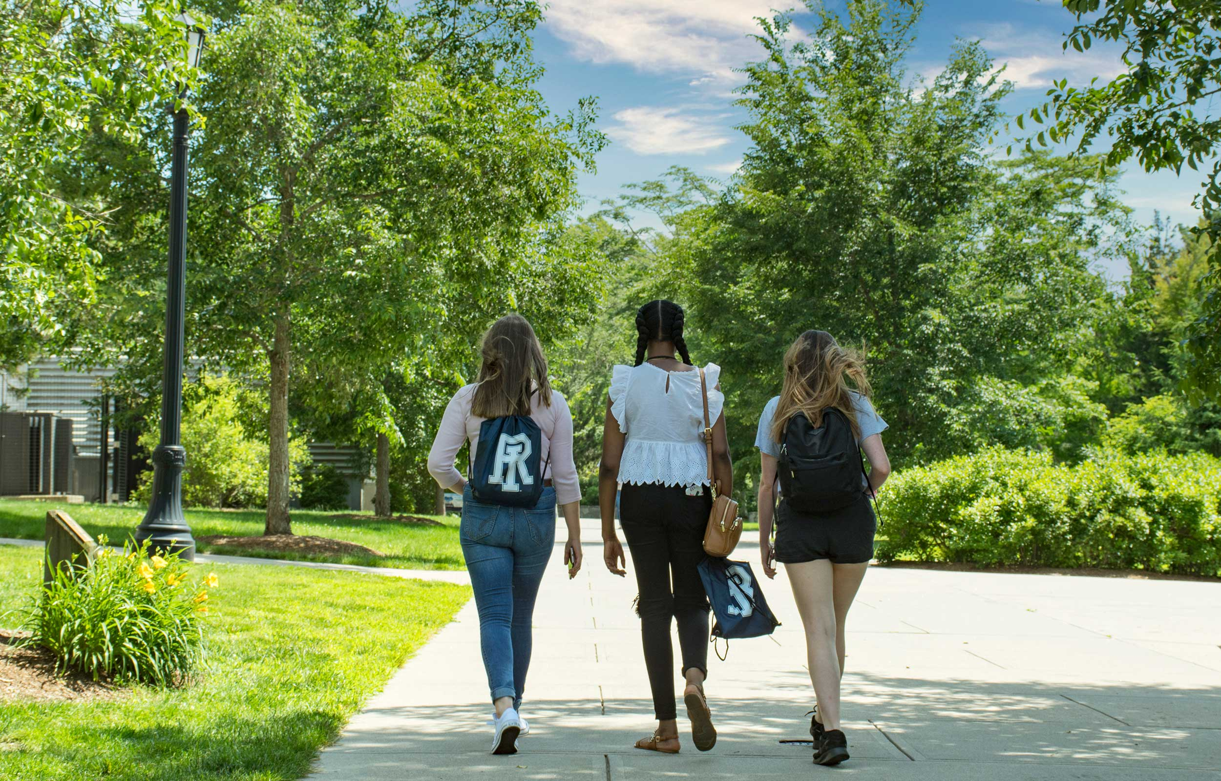 Three students walking together (back view) on campus in the spring