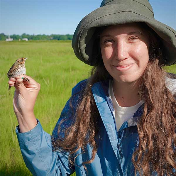 Coastal Fellow Jessica Szpila poses with endangered sparrow the subject of her research